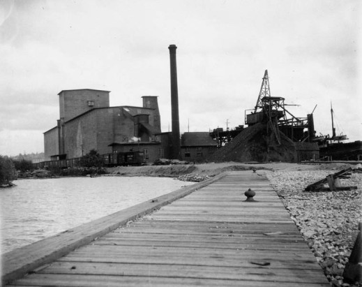 A black-and-white photograph showing a long wooden dock by the shore and grain elevators in the background