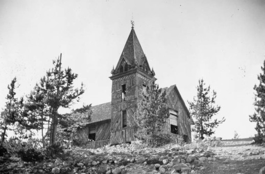 A black-and-white photograph of an abandoned wooden church