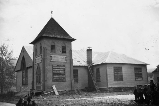 A black-and-white photograph showing a boarded-up church with construction material scattered around it