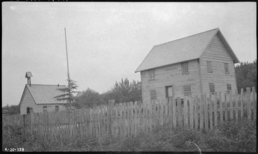 A black-and-white photograph showing two small abandoned buildings, one possibly a school, behind a white picket fence