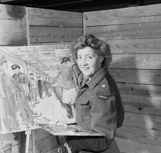 A black-and-white photograph showing Molly Lamb Bobak posing in front of an easel with brushes and palette in hand. Bobak wears an army battledress jacket and smiles at the camera. The partially completed painting behind her depicts male and female members of the Canadian Army standing inside a room.