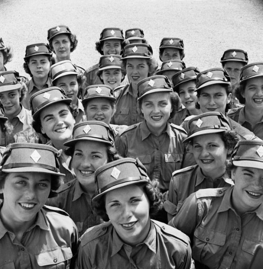 A black-and-white photo showing a crowd of smiling CWAC recruits. They wear summer dress uniforms and caps with diamond-shaped cap badges.