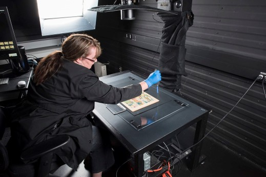 A comic book is placed on a flat black surface underneath a sheet of Plexiglas. A woman leans over the surface, using an anti-static blower to remove dust from the Plexiglas. The lens of a camera is visible above the table.