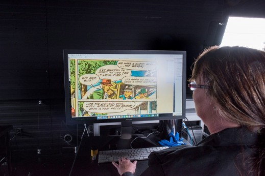 A woman faces a computer monitor showing an image of a page from a comic book.