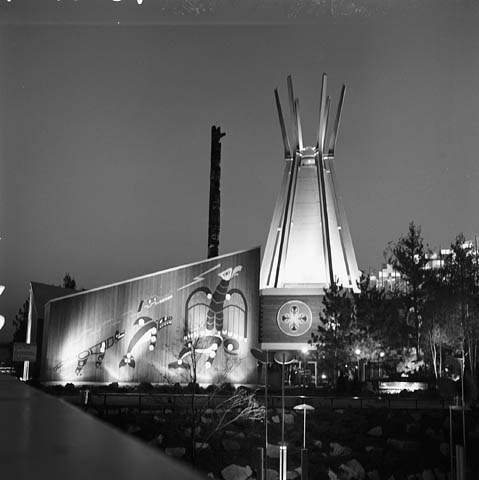 A black and white photograph of a building with native art on the front wall and a tipi-like structure adjacent to it. The top of a totem pole can be seen behind the building.