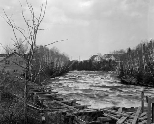 A black-and-white photograph showing a river with a heavy current, trees on both sides, and an old mill to the left in the background