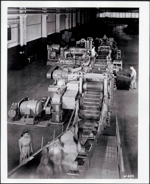 Black and white photograph showing workers operating a machine used to roll the steel and make it into panels.