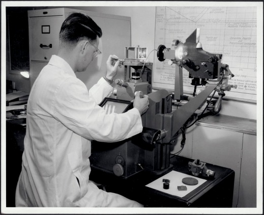 Black and white photograph of a man in a white lab coat taking a photomicrograph.