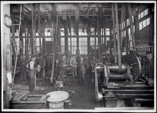 Black and white photograph showing men in a plant. A large number of workers manually operating the first mechanical machines can be seen in the background.