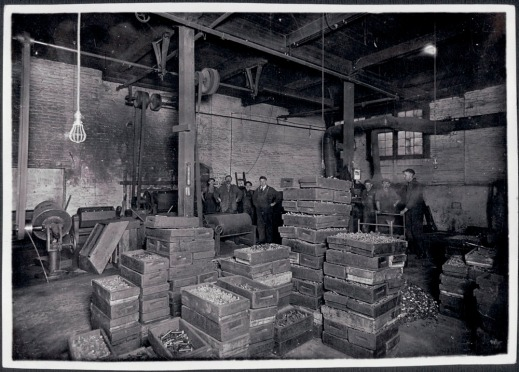 Black and white photograph showing employees packing products inside a plant.