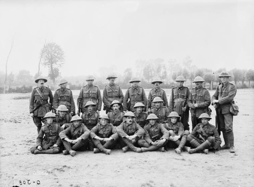 A black-and-white photograph of a group of soldiers in uniform in a field.
