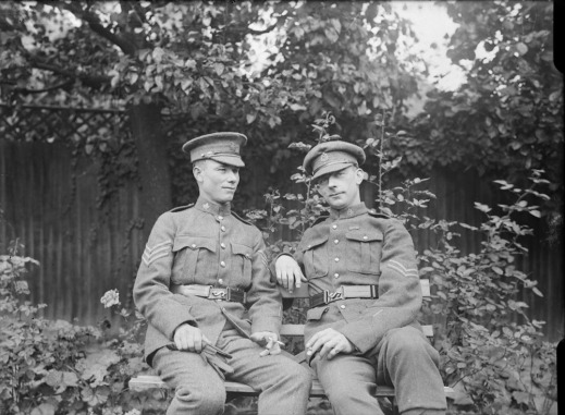 A black-and-white photograph of two soldiers in uniform sitting on a bench. The man on the right is looking directly at the camera with a slight smile.