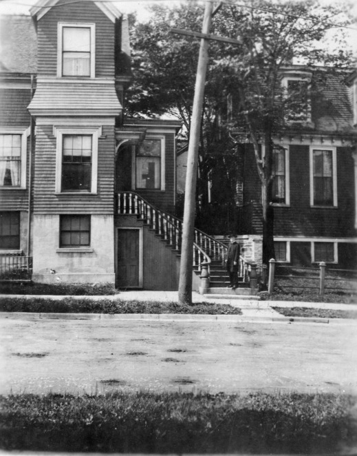 Black-and-white photograph featuring Dr. Edward M. Saunders, standing on the front staircase of a three-story Victorian style house. Dr. Saunders is wearing a black clerical suit and a black hat. The photograph was taken from across a residential street.