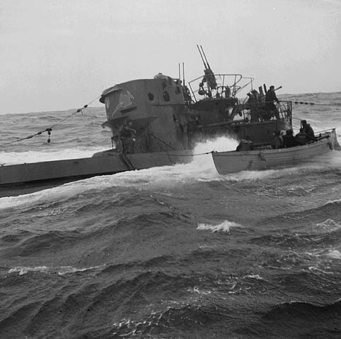 Black-and-white photograph showing a submarine and a whaler side by side. Members of the submarine's crew can be seen on the bridge. The people in the whaler are seated.