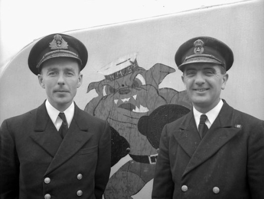 Black-and-white photograph, showing two men in naval uniform posing in front of the nose turret of their corvette. Between the two men, an image painted on the turret shows a bulldog standing on his hind legs, wearing a sailor hat and boxing gloves.