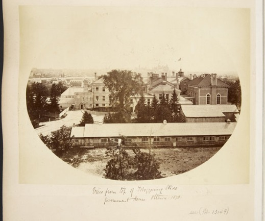 A yellow and brown image on albumen photographic paper of a winter scene in Ottawa, including several buildings, a road, and trees.
