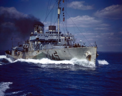Colour photograph of a Royal Canadian Navy corvette under way at top speed. Thick black smoke pours from a funnel. Number K145 is written in black on the grey vessel.