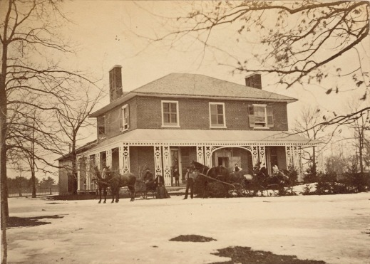 A black and white image of a house with melting snow all around. In front of the house are two horse-drawn sleighs with people around them.