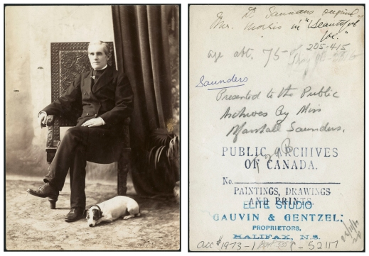 Black-and-white photograph of a middle-aged man sitting in an ornate chair with a small dog, possibly a Russell terrier, laying at his feet. The man is wearing a black clerical suit. Dark drapery and a potted plant appear in the right of the portrait. The back of the photograph includes a stamp from Gauvin & Gentzel Studio.