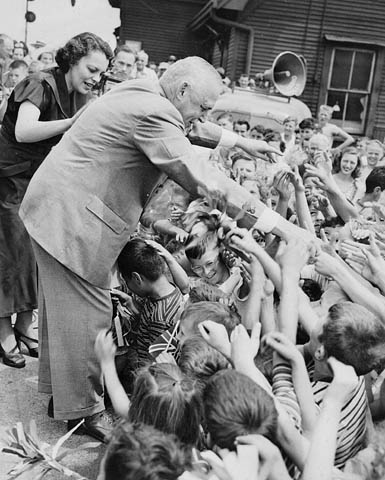 An older man is standing on a stage and reaching out to a crowd of children.