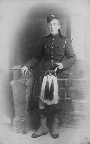 A black-and-white photograph of a young man wearing a kilt and sporran, holding a baton in his left hand and leaning on a sculptural shelf.