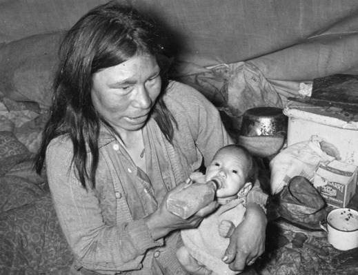 Black and white photograph of a gaunt looking Inuit woman and child sitting in a small tent with cooking supplies in the background. The woman is feeding the baby with a rectangular bottle.