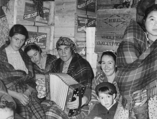 """Black and white photograph of five women, four of them seated and one on the far right standing with a baby wrapped in a plaid shawl. The woman in the centre of the photograph is playing an accordion, and the woman to her left has a young boy in her lap. Behind them are several wooden crates labeled """"Marven's Biscuits"""" and one marked """"H.B.C. Wholesale Vancouver."""""""