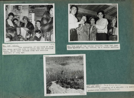 """Photograph of a green album page with three black and white photographs (numbered 158, 159, and 160) with typed captions on white paper. The photograph in the top left corner is of women and children sitting in front of several wooden crates labeled """"Marven's Biscuits"""" and one marked """"H.B.C. Wholesale Vancouver."""" The photograph in the top right corner is of two couples dancing while a woman plays the accordion. The photograph at the bottom of the page is of an Arctic ground squirrel in a grassy field with a rock in the foreground."""