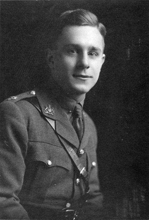 A black and white portrait showing a young man in uniform. He sits facing the camera and sports a slight smile.