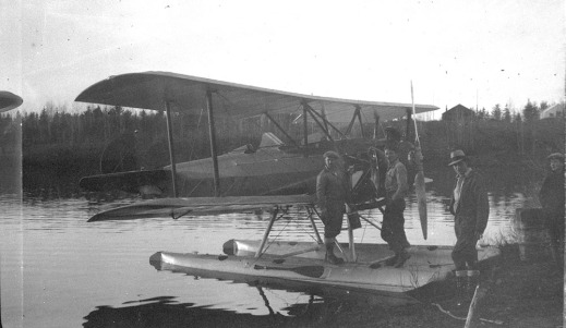 A black-and-white photograph showing a floatplane at the edge of a lake. Two figures stand on the floats near the propeller and a third figure stands on the shore to the right. A fourth figure, partially in view on the far right, looks at the plane.