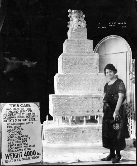 A black-and-white photograph of a giant cake with a young woman standing on one side of the cake and on the other side is a poster with a list of ingredients contained in the cake.