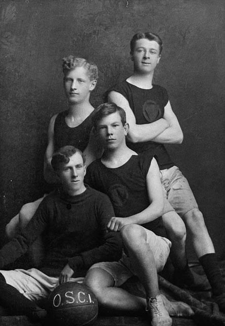 A black-and-white photograph showing four young men posing around a basketball.