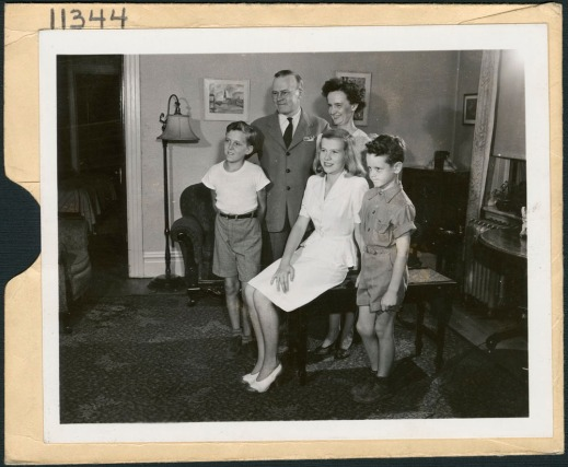 A black-and-white photograph of a family group, including a woman, man and three children in a living room.
