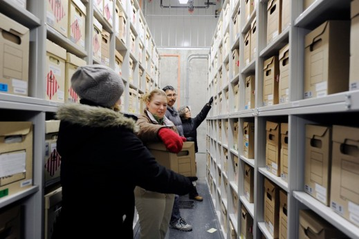 A colour photograph of four people wearing winter coats standing in the middle of an aisle between shelving and placing boxes on the shelves.