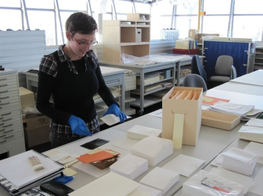 A colour photograph of a woman wearing nitrile gloves and taking a negative out of an envelope. The table in front of her is full of envelopes and archival boxes.