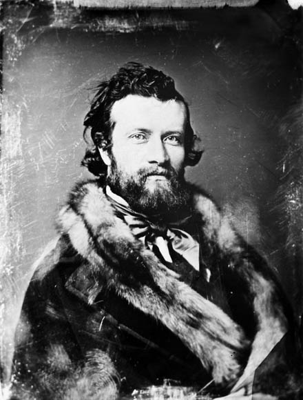 A black-and-white photograph of a young, bearded man looking directly at the camera. He is wearing a fur coat and a very dapper cravat.