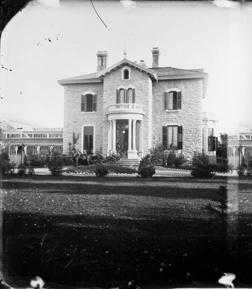 A black-and-white photograph of a large, stately home with a central doorway and windows on each side. There is a horse-drawn carriage in the driveway.