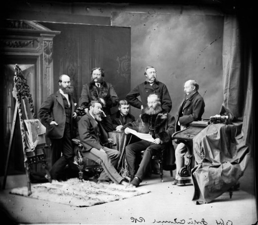 A black-and-white studio photograph of a group of men in various poses, facing in different directions.