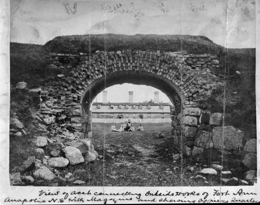 Black-and-white photograph of a stone archway and the view through it showing a large fenced building in the background with land in front. A woman and five children are pictured in the centre, seated on the ground.