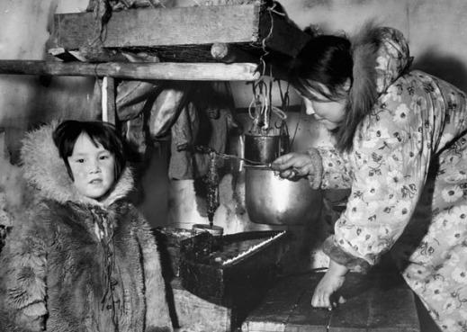 Black-and-white photograph of an Inuit woman inside an igloo wearing a floral print parka and tending a seal oil lamp, with a young Inuit child wearing a fur parka.