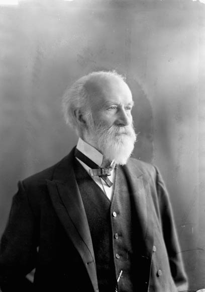 A black-and-white photo of an older man wearing a suit jacket, waistcoat and bow tie.