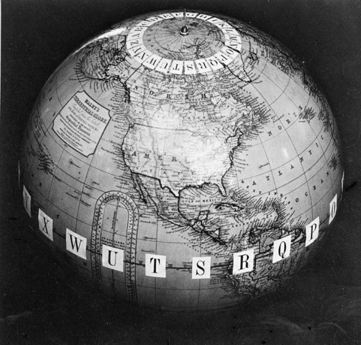 A black-and-white photograph of a terrestrial globe showing the North American continent with letters at each meridian around the North Pole and at the equator.