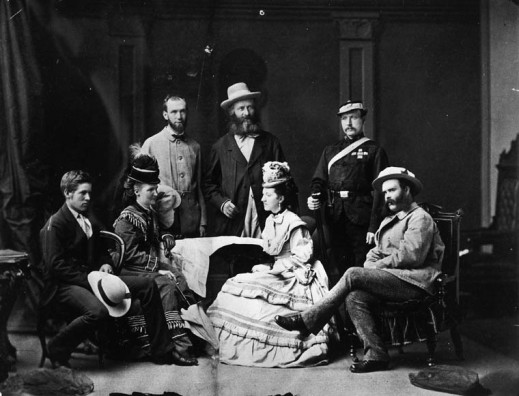 A black-and-white photograph of a group of people. Two women are seated facing each other with two seated men beside them, and behind them stand three other men.