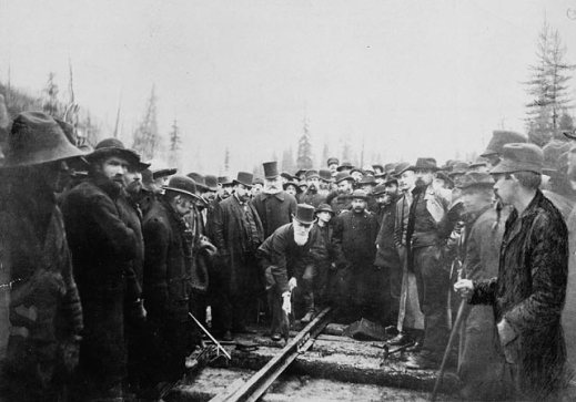 A black-and-white photograph of a man hammering a train track. He is surrounded by a large group of men, some of them are looking at the camera and others are looking at the train track.