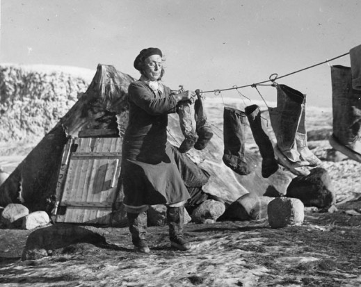 A black-and-white photograph of a woman standing in front of a tent, hanging seal boots to dry on a clothesline.