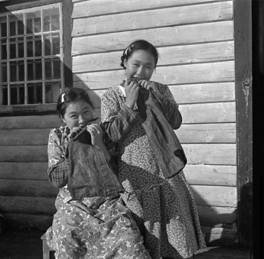 Black-and-white photograph of two Inuit girls in front of a wooden house, each chewing on a boot-shaped piece of sealskin.