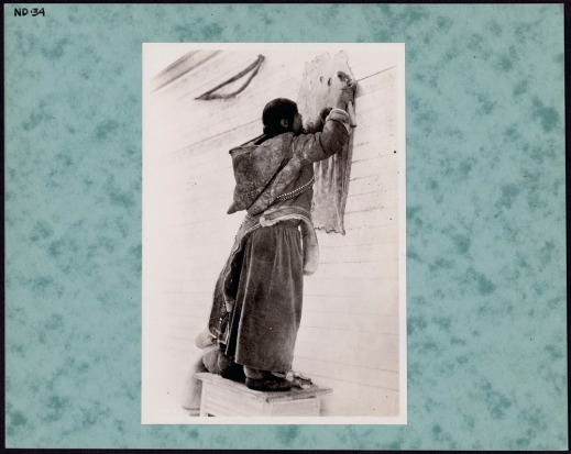 Black-and-white photograph of an Inuit woman wearing a skin parka and long skirt and standing on a wooden crate, with her back to the camera, scraping a sealskin that is fastened to a clapboard wall.