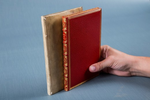 A hand holds two books upright against a grey-blue background. The book on the left is in a very plain beige cover. The book on the right is in a red cover decorated with gold.