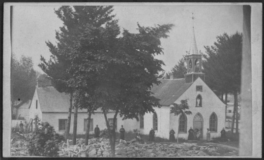 Black-and-white photo of a church set among trees with church goers standing along the walls.