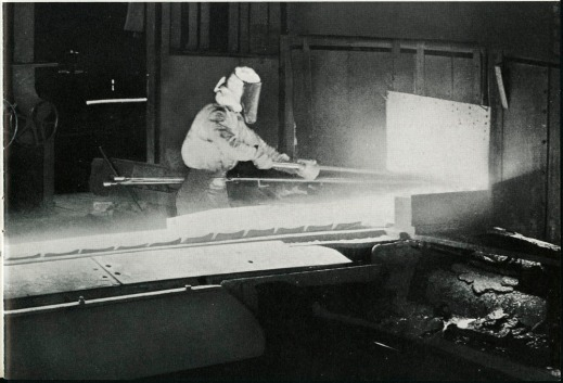 Black-and-white photograph of a labourer working on a bar of hot iron.